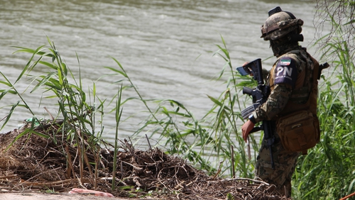 Mexican police patrol the area where the bodies of Oscar Ramirez and his daughter were found