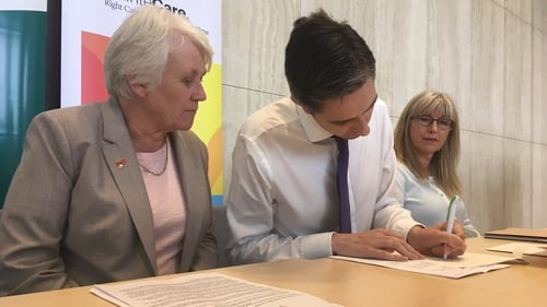 Minister of State Catherine Byrne (L) watches as Simon Harris signs the legislation