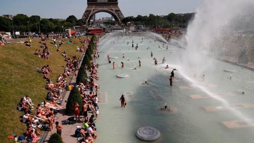 People bathe in the Trocadero Fountain near the Eiffel Tower in Paris