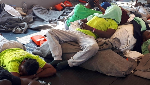 Migrants resting on a boat in the Mediterranean Sea