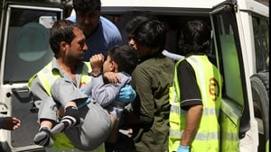 An injured child is carried to an ambulance following the blast