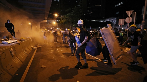 Police fire tear gas to disperse protesters outside the Legislative Council Building