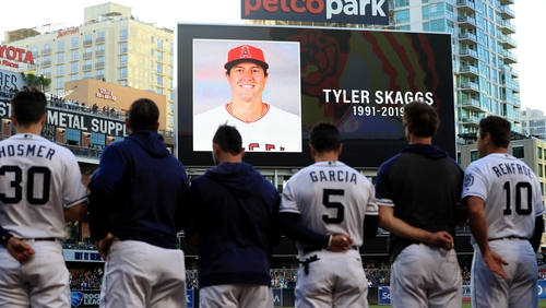 Players for the San Diego Padres and San Francisco Giants stand during a moment of silence for pitcher Tyler Skaggs of the Los Angeles Angels