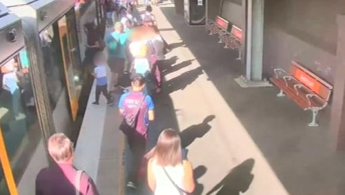 The young boy fell as he tried to board the train with his mother