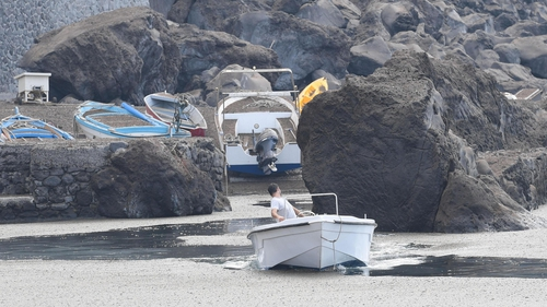 A boat leaves the port of 'Pertuso' as the coastline is seen covered with a layer of volcanic ash