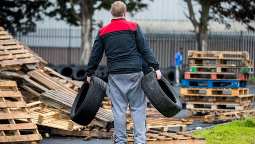 A man carries away tyres from the bonfire at the Avoniel Centre