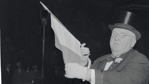 Baron of Broadway outside No. 10 Downing Street in 1955, unfurling the Irish flag. Photo Credit: Getty Images