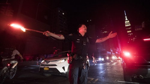 A police controls traffic after a massive power failure hit parts of Manhattan, in New York