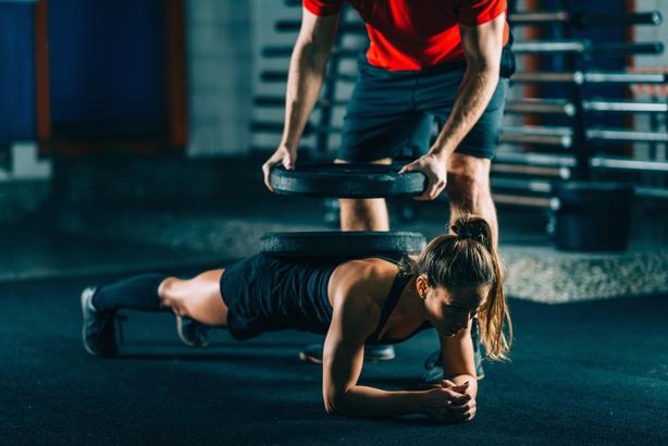 Cross training. Female athlete resisting weight of heavy barbells