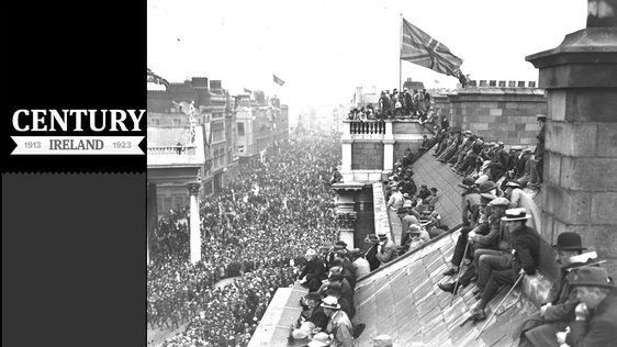Century Ireland Issue 157 A victory parade celebrating the end of the First World War, in Dublin in July 1919. In the foreground people sit on the roof of Trinity College Dublin to look down on the parade. Westmoreland Street is visible in the background.