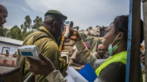 A healthworker screens people for Ebola symptoms in eastern Democratic Republic of Congo