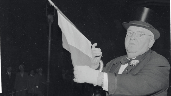 John J. Hanley, the 'Baron of Broadway' holds up an Irish flag in London, where he tried to buy the Northern Ireland from the British.