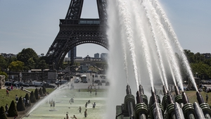 People cool down at the fountains of Trocadero, across from the Eiffel Tower