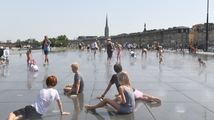 Children cool off at the Water Mirror on the Place de la Bourse in Bordeaux as temperatures reach 42C