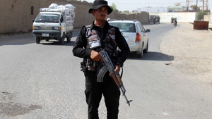 An Afghan security official keeps watch at a checkpoint on a roadside in Kandahar