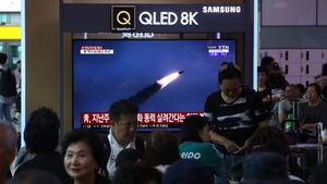 South Koreans watch on a screen a file image of reporting North Korea's missile launch