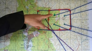 A Royal Malaysian Police officer points to a map showing the search and rescue operation area