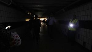 People walk in darkness at Clapham Junction railway station