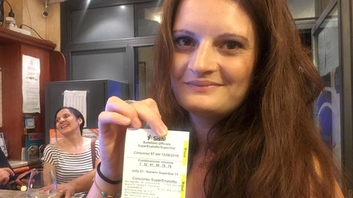 The bar's owner Sara Poggi shows the receipt of the winning ticket in the SuperEnalotto lottery