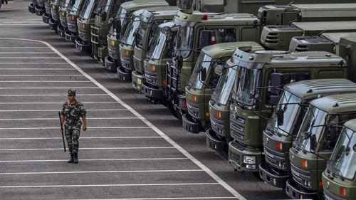 A member of China's People's Armed Police Force walks by vehicles gathered on the Shenzhen Bay Sports Centre