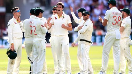 Australia's Pat Cummins (centre) celebrates taking the wicket of England's Chris Woakes
