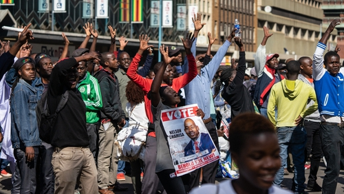 Scores of people gathered in the capital's Africa Unity Square to demonstrate against the country's worsening economy