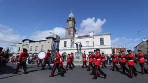 A band marches past the Ulster Defence Force memorial in Lisburn