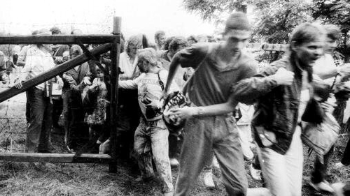 East German citizens break through a gate of the fence separating Hungary and Austria on the border between the two countries near Sopron during the Pan-European Picnic on 19 August 1989