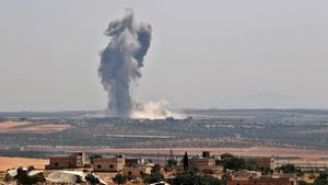Smoke billows above buildings during a reported air strike by pro-regime forces on Khan Sheikhun yesterday