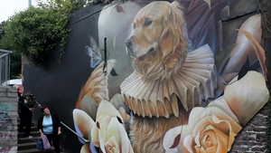 A woman looks over a mural titled 'Ned The Dog' by Curtis Hylton