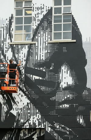 Artist HUARIU uses cherry picker to finish off his mural