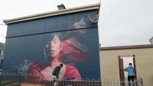 Artist Spear works on a mural titled 'Karelis' for the festival