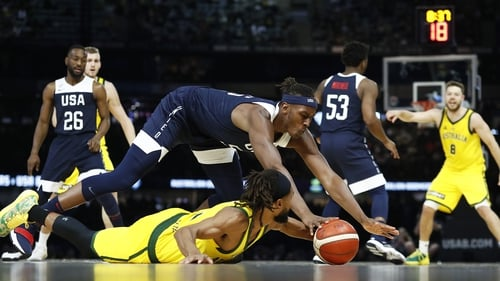 Australia's Patty Mills, on the floor, and Myles Turner of the USA contest the ball.