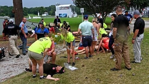 Fans are assisted by medical personnel after a lightning strike