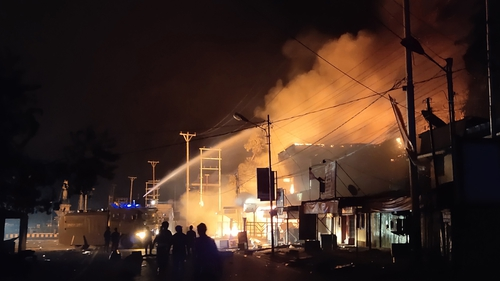 Firefighters battle to put out a burning building that demonstrators set it on fire