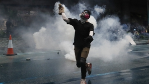 A protester wearing a gas mask throws back a tear gas after police fired tear gas during an anti-government rally