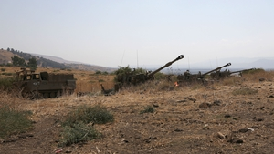 Israeli self-propelled artillery guns are positioned near the Lebanese border