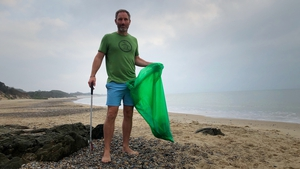 Seán Ferguson collects discarded buckets and spades, along with other rubbish, before his daily swim at sunrise