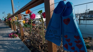 A pair of diving fins and flowers at a memorial wall near the Truth Aquatics moorings in Santa Barbara