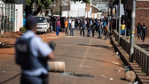A group of men gather in front of a police station in Johannesburg's CBD as the unrest continues