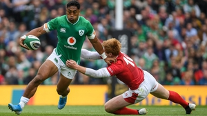 Bundee Aki of Ireland is tackled by Rhys Patchell at the Aviva Stadium