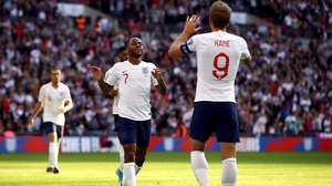 Raheem Sterling celebrates scoring his side's third goal at Wembley with England captain Harry Kane