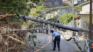 A police officer ispects a fallen utility pole downed by winds caused by Typhoon Faxai in Kamakura