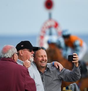 Racegoers snap selfies near the winning post at Laytown
