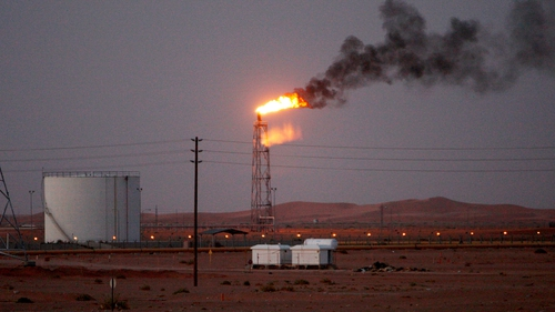 A gas flame behind pipelines in the desert at Khurais oil field