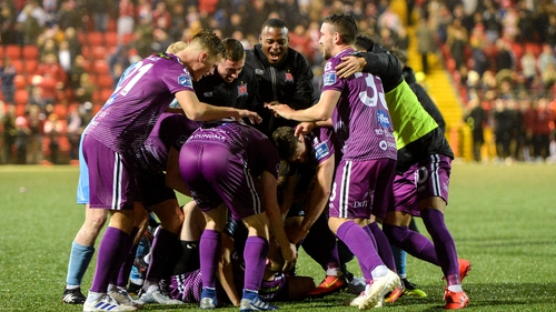 Dundalk players mob Chris Shields after he scored the winning penalty