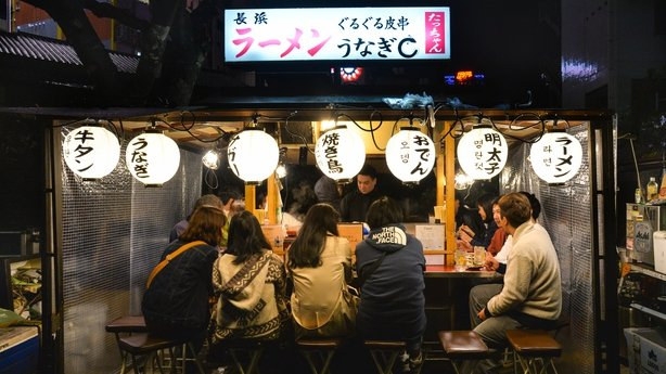 People are having dinner at Yatai, local food stand, along the river near Canal city, Fukuoka, Japan