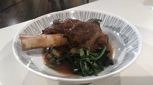Lamb shanks with aubergine and kale.