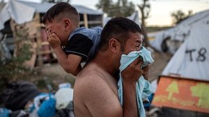 A man and a boy react after police fired tear gas during clashes outside the refugee camp of Moria