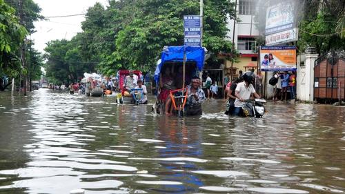 People use rickshaws to cross a flooded street in Patna, Bihar, India